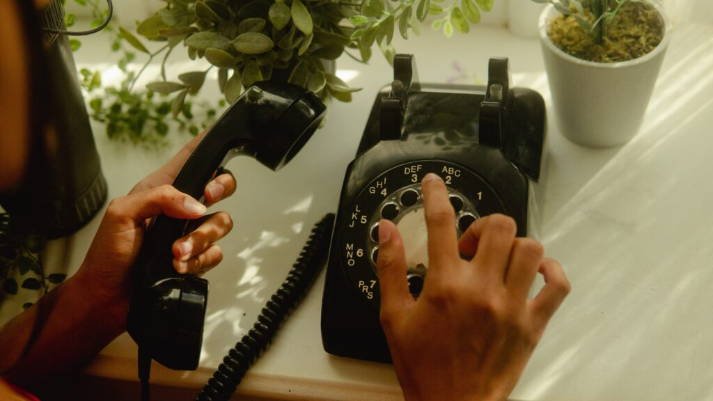 A LADY USING AN OLD PHONE